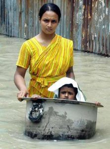 Bangladeshi woman with her child wading through flood waters in Sirajgonj , about 100km northwest of Dhaka